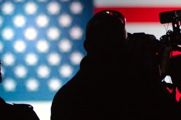 A man with a video camera silhouette; American flag in background.